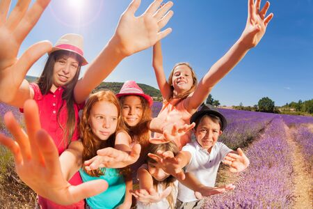 Exited kids in lavender field waving their hands