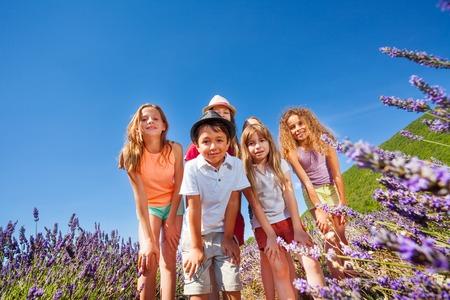 playmates: Niños felices de pie juntos en el campo de lavanda