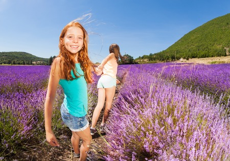 Girl pulling friend holding hand in lavender field Stock fotó
