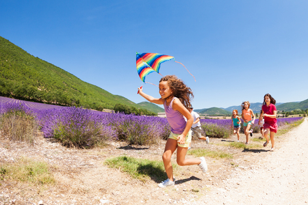 Cute girl running with kite through lavender field
