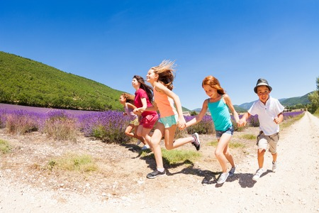 Group of happy children running in lavender field