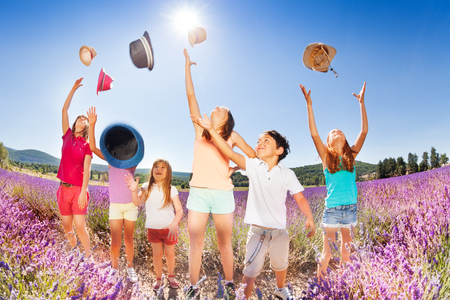 Happy kids tossing up hats over blue sky in summer
