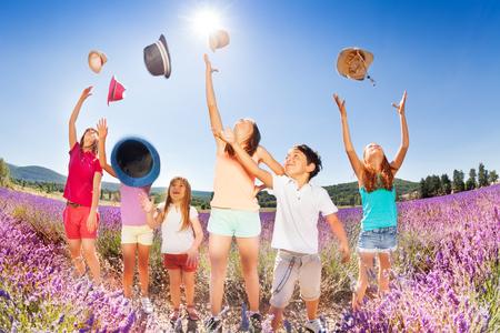 playmates: Niños felices arrojando sombreros sobre el cielo azul en verano Foto de archivo