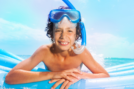 Boy with scuba mask swim on matrass in the sea