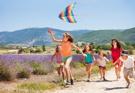 Kids having fun flying colorful kite in summer Stock Photo
