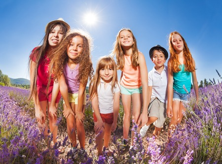 Kids enjoying summer standing in lavender field
