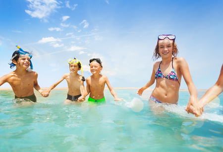 Girls and boys running in shallow water together Stock Photo