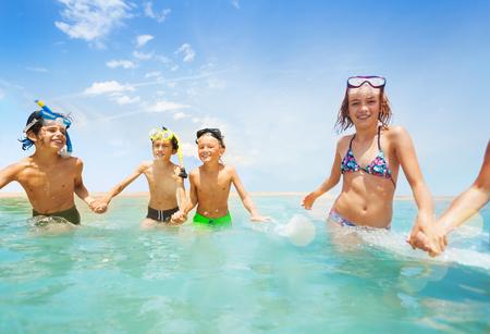 Meisjes en jongens lopen samen in ondiep water