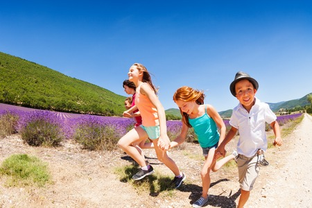 Boys and girls running together in lavender field Stock Photo