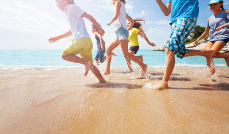 Close-up of running kids legs in shallow sea water Stockfoto