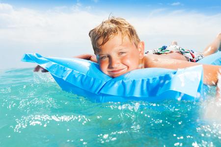Leuke knappe jongen zwemmen op matras in zee Stockfoto