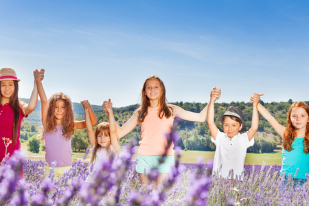 Happy kids holding hands up in lavender field
