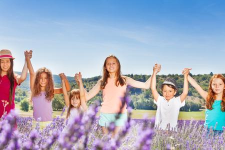 playmates: Niños felices levantando las manos en el campo de lavanda Foto de archivo