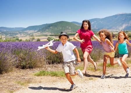 Three girls hurry after boy holding toy plane Standard-Bild