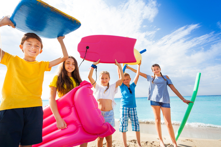 Group of happy kids came to swim on sandy beach Banco de Imagens