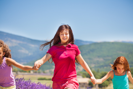 Girl running with her friends in lavender field Stock Photo
