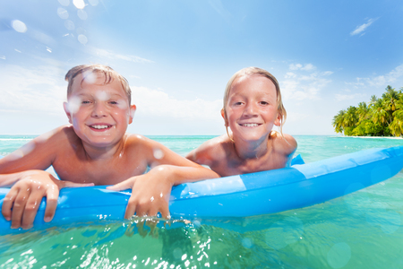 Two boys on inflatable matrass in the sea