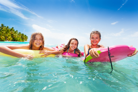 Three girls swim in the sea on surfboards Imagens
