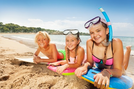 Cute kids enjoying sun on sandy beach