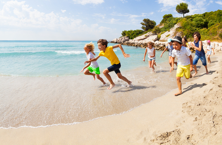 Group of happy kids racing on sandy beach