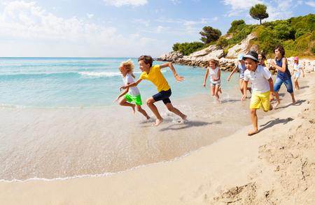 Gruppo di ragazzi felici che corrono sulla spiaggia sabbiosa Archivio Fotografico - 87845560