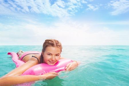 바다에 핑크 matrass에 한 어린 소녀