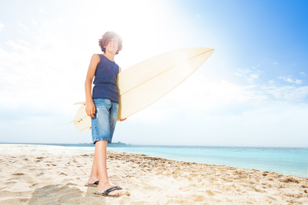 Sunlit portrait of teenager with surf board Stock fotó