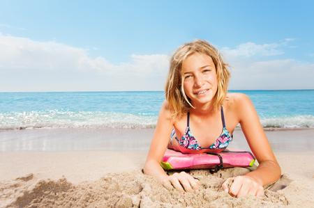 Het blonde meisje met surfplank legt op overzees strand