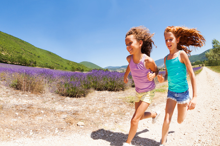 Two happy girls running together in lavender field