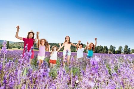 playmates: Niños de pie en el campo de lavanda y tomados de la mano Foto de archivo