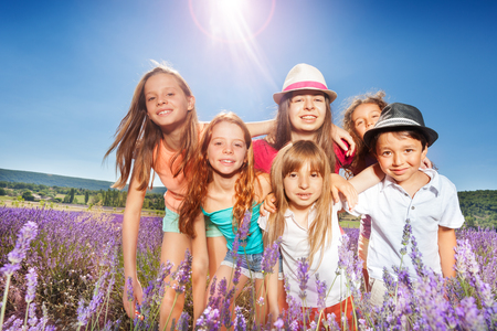 Cute kids standing in lavender field at sunny day Stock Photo