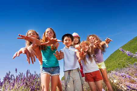 Kids reaching out their hands to camera outdoors Stock Photo