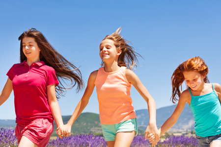Three happy girls running together outdoors Stock Photo