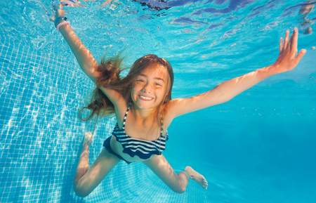 Girl swimming and diving in blue pool with fun Stock fotó