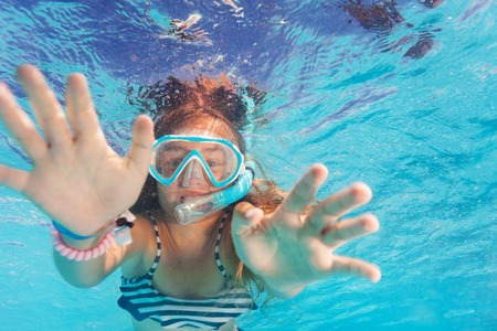Cute little girl snorkeling in the pool Stock Photo