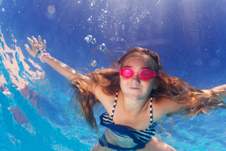 Girl in goggles learning holding breath underwater Stock Photo