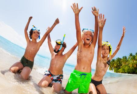 Los niños se sientan en la playa con máscaras de buceo levantan las manos