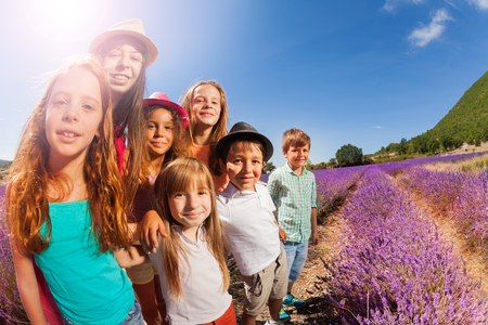 Happy kids standing in lavender field at sunny day