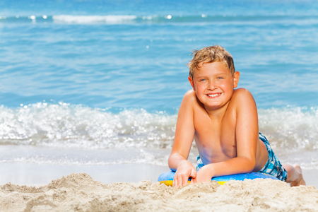 Handsome plump boy on summer sea vacation lay on the beach on body board for surfing ready to go swimming Stock Photo