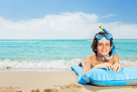 Boy on beach with inflatable matrass in scuba mask Stock Photo