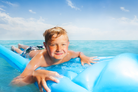 Boy on the blue matrass swim in sea Stock Photo