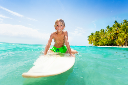 Blond kid swimming on surf board in clear sea