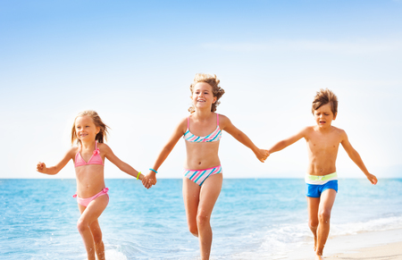 Happy friends running together along sandy beach Stock Photo
