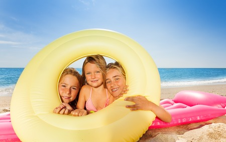 Cute girls looking through rubber ring at beach Stock Photo