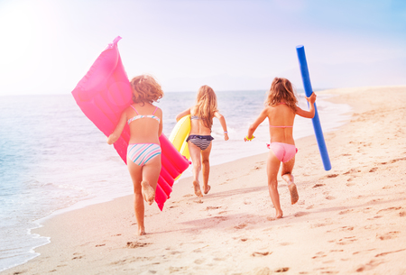 Girls running with swimming tools along the sea