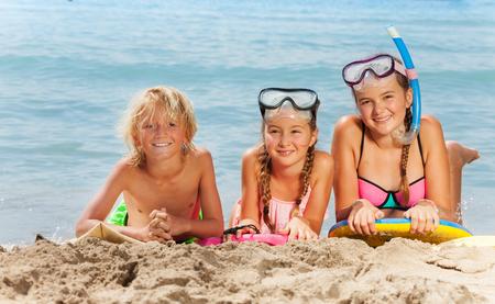 Glückliches Lächeln der Jungen und der Mädchen auf dem Strand Standard-Bild - 88775810