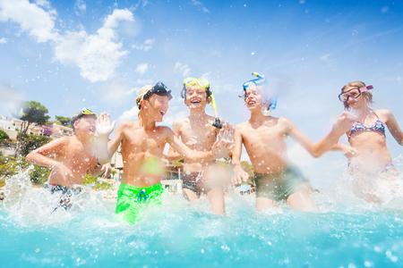 Veel jongens rennen samen in een groep de zee in