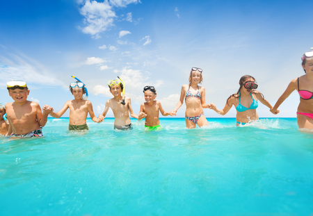 Group of kids holding hands walk in the sea water