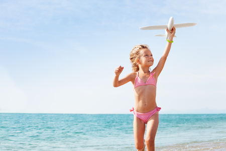 Happy little blond girl in pink swimsuit playing with white toy plane on the seashore in summer Foto de archivo