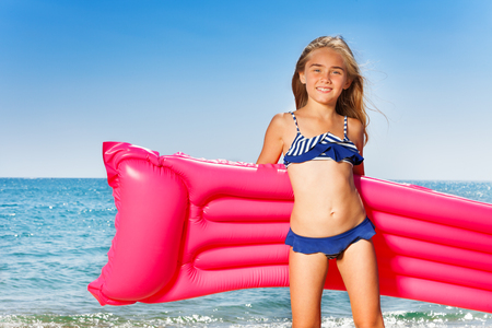Young girl in bikini with pink inflatable mattress
